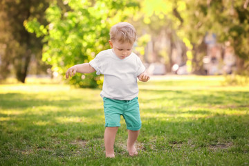 Cute baby boy walking in green park on sunny day