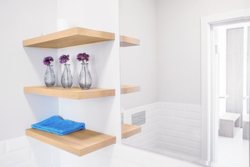 Interior of light modern bathroom with decorative elements on shelves