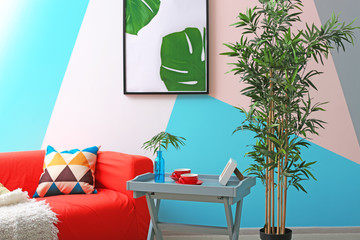 Modern living room design with framed picture of tropical leaves