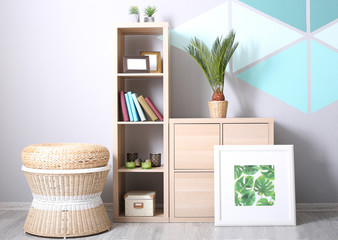 Modern room design with framed picture of tropical leaves, bookcase and sago palm