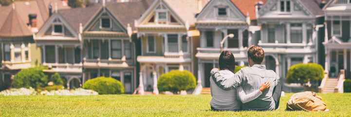 San Francisco tourist attraction at Alamo Square, the Painted Ladies banner panorama, California travel. Couple tourists relaxing in grass enjoying popular destination. People lifestyle