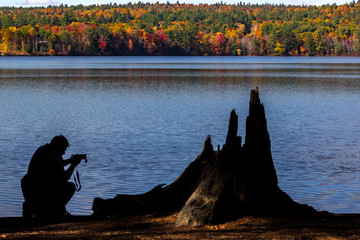 Silhouette of photographer on a lake in the fall