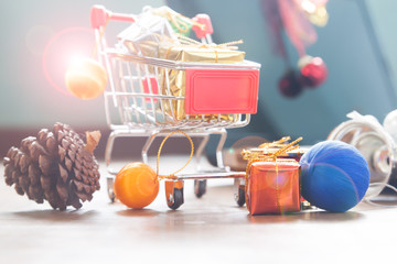 Close up of shopping cart with gift boxes and Christmas decoration