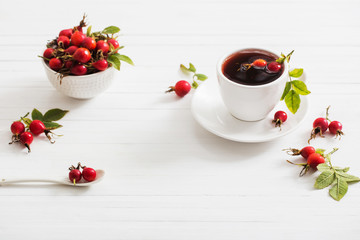 tea with berries of a dogrose on a wooden background