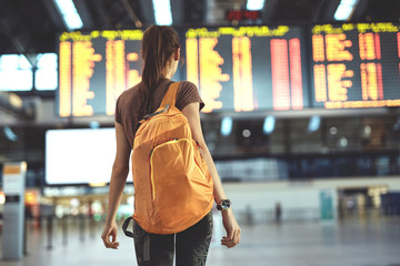 Young woman with small backpack as a hand luggage in international airport looking at the flight information board, checking her flight Wall mural
