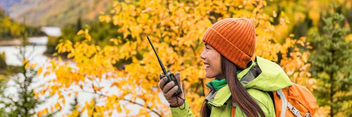 Autumn hiker girl talking on ham radio portable transceiver . Amateur radio operator woman holding handheld walkie-talking in outdoor nature landscape banner panorama crop. Active lifestyle.