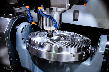A modern CNC milling machine makes a large cogwheel.