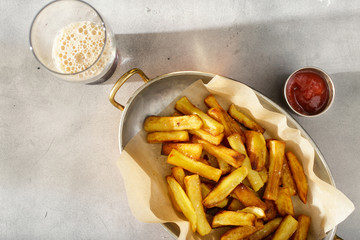 Pan of homemade french fries with ketchup and dark beer