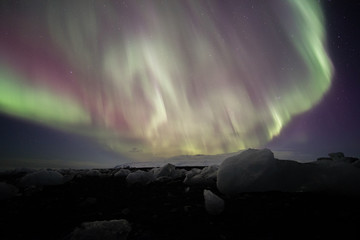 aurora borealis over black sand  beach and ice cubes, iceland.