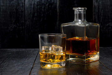 whiskey with a decanter on a wooden background
