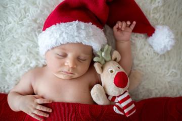 Little sleeping newborn baby boy, wearing Santa hat
