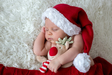 Little sleeping newborn baby boy, wearing Santa hat