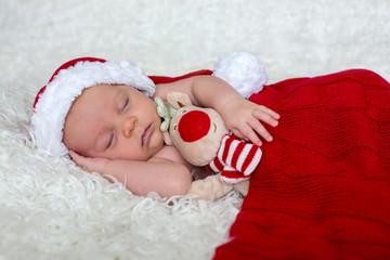 Little newborn baby boy, wearing Santa hat