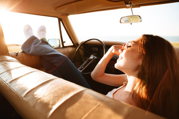 Image from car of pleased brunette woman lying on seat