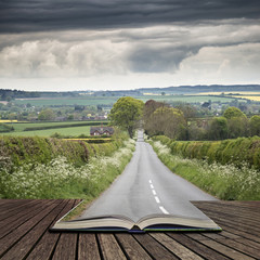 Landscape image of empty road in English countryside with dramatic stormy sky overhead concept coming out of pages in open book