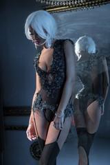 Girl in black lingerie - body, near the mirror.