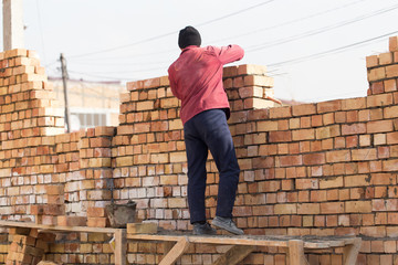 Worker builds a brick wall in the house