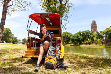 Young asian female traveler with backpack traveling sitting on taxi or Tuk Tuk and seeing photo on vintage camera with Wat Mahathat background, Ayutthaya Province, Thailand