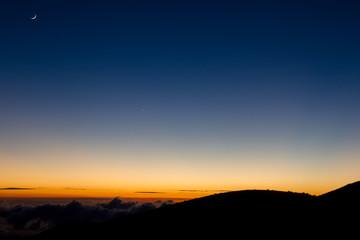 Mondsichel über dem vom Sonnenuntergang erleuchteten Horizont am Mauna Kea auf Big Island, Hawaii, USA.