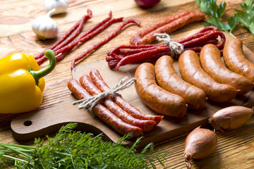 Fresh raw sausages with vegetables on wood