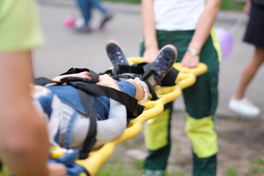 The rescue service evacuates the injured child on stretchers