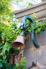 small bronze bell on a stone wall