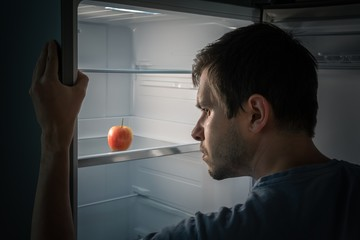 Hungry man is looking for food in fridge at night. Only apple is inside empty fridge.