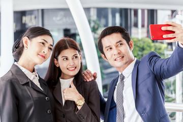 Business people taking selfie on smartphone outside office