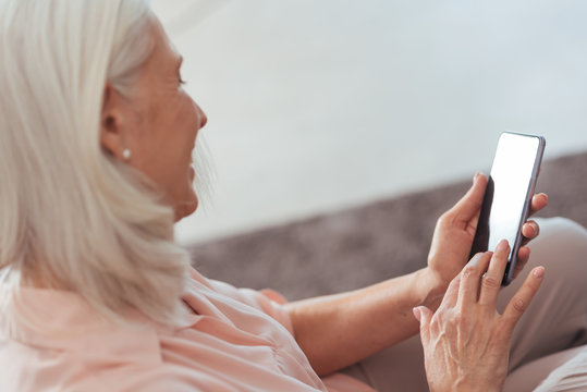 Cheerful senior woman using her smart phone at home