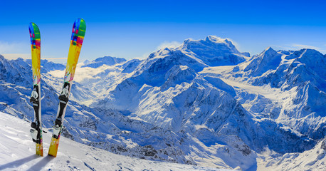 Wall Mural - Skiing in winter season, mountains and ski equipments on the top of snowy mountains in sunny day. Swiss Alps.