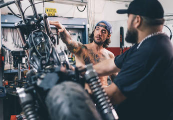 Man biker with tattoos poses with mechanic in workshop