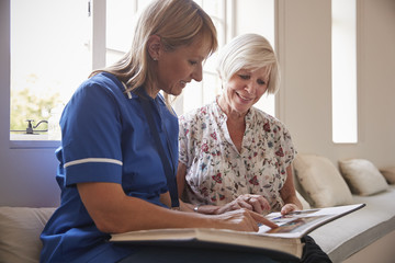 Senior woman sitting looking at photo album with nurse