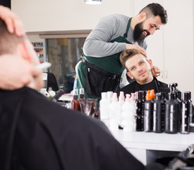 Happy man hairdresser making haircut to client