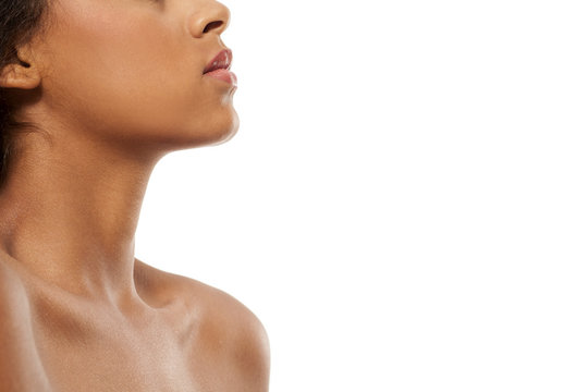Profile of dark skinned woman's chin, neck, and naked shoulders