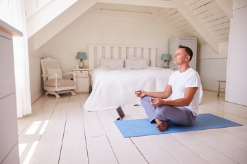 Mature Man With Digital Tablet Using Meditation App In Bedroom