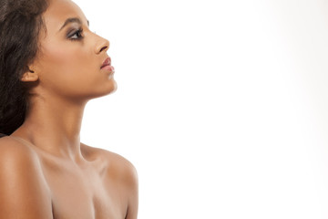 Profile of serious young dark-skinned woman on a white background