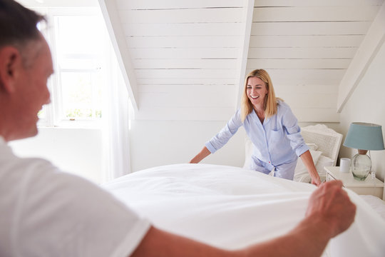 Couple Wearing Pajamas Making Bed In Morning