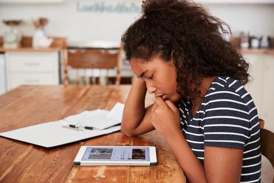 Teenage Girl At Home Using Digital Tablet Being Bullied On Line
