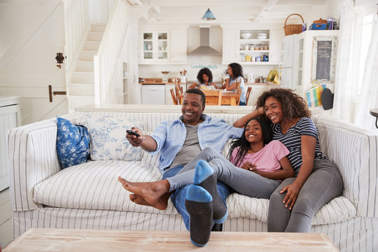 Father Sitting On Sofa Watching TV With Teenage Daughters