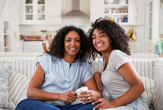 Portrait Of Mother Sitting With Teenage Daughter On Sofa