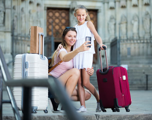 cheerful mother with daughter travelers and taking selfie