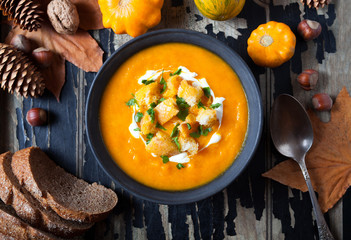 Pumpkin and carrot soup with cream and crackers, croutons autumn food dish for Thanksgiving, halloween on dark old wooden background. Top view. close up. Flat lay autumn vegetables.