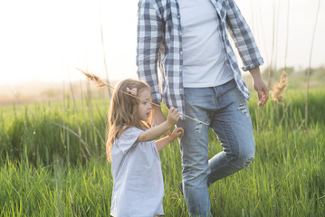 father and daughter walking in high grass field