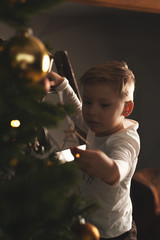 Adorable child decorating Christmas tree at home