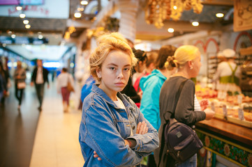 young beautiful woman in jeans clothes in business space of shopping center. portrait of a girl with freckles on her face, stylish girl standing near show-windows of fair in shopping center