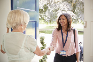 Senior woman greeting female care worker making home visit Wall mural