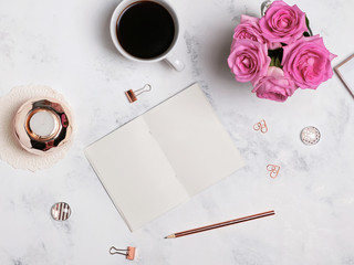 Coffee, flowers, gold colored stationery and blank notepad, top view