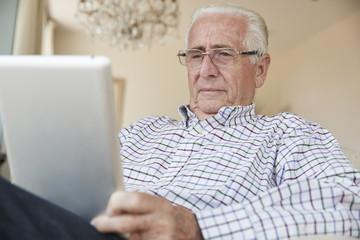 Senior man using a tablet computer at home, close up
