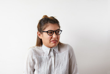Negative human expressions, emotions, feelings, reaction and attitude. Studio shot of young Caucasian female employee wearing glasses and formal shirt, grimacing, having displeased disgusted look