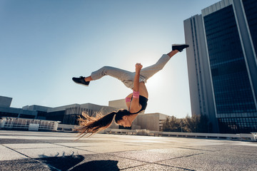 Urban woman performing a frontflip in city